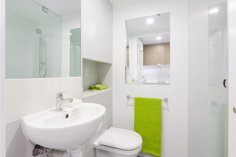 Modern en-suite bathroom in Wright College room, showing shower, sink, toilet, mirrors, storage and towel rail.